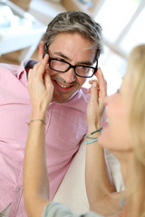 Woman putting eyeglasses to husband