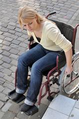 Rollstuhlfahrerin vor Hindernis