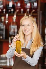 freundliche verkäuferin zeigt eine kleine flasche öl