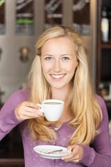 blonde frau genießt eine tasse kaffee