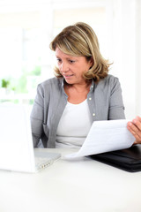 Senior woman using internet to get some help with paper work