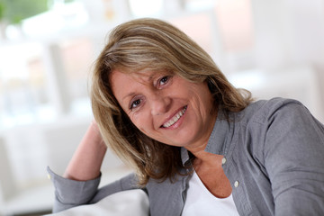 Senior woman at home sitting in sofa