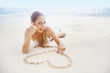 young beautiful woman on the beach making heart on the sand