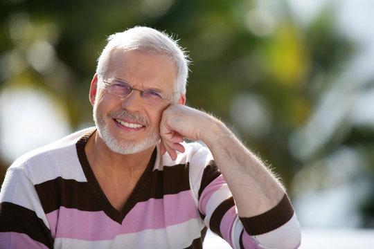 Happy senior man sitting in the sunshine