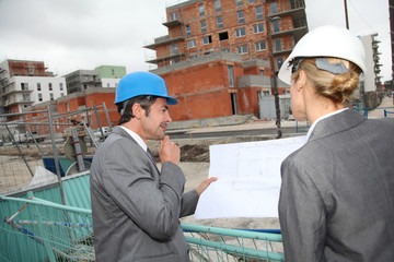 Construction engineers checking plans on building site
