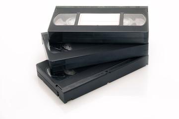 Три VHS видеокассеты на белом фоне.