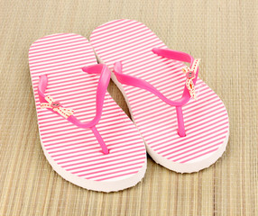 Pink beach slippers on mat