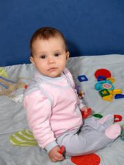 Младенец держит в руках игрушки