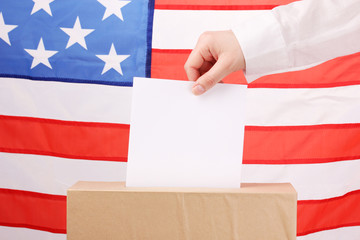Hand with voting ballot and box on Flag of USA