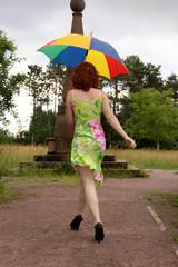Frau geht mit Schirm im Regen