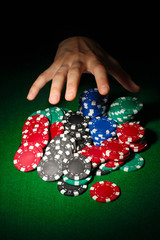 Poker chips and hand above it on green table