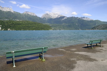 Annecy lake and mountains and green wooden bench