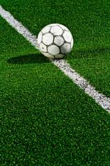 Old soccer ball on green grass
