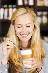 lächelnde blonde frau mit latte macchiato