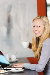 blonde frau mit laptop im café
