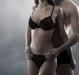 Bodies of a young and sexy couple in black erotic lingerie