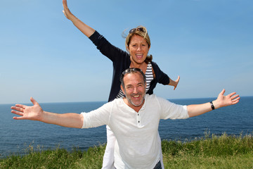 Cheerful couple stretching arms in front of the sea