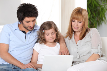 Parents helping their child with her homework