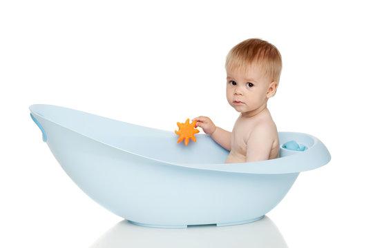 Boy in blue bath tub on white background
