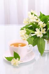 Cup of tasty jasmine tea and flowers