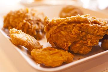 Fried chicken on white disk .