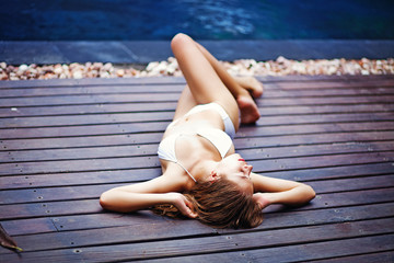 Young woman in swimsuit lying on the wooden floor outdoors
