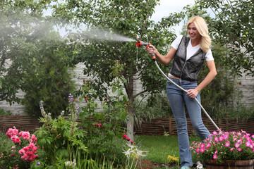 Beautiful woman watering garden