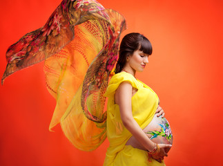 The pregnant girl with the drawn picture on a stomach in a yello