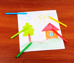 Children's drawing of house and pencils on wooden background