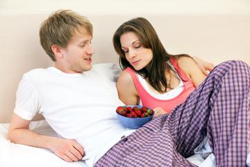 Verliebtes Paar im Bett mit Erdbeeren
