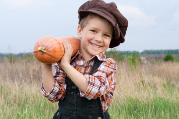 Smiling boy with pumpkin on his shoulder