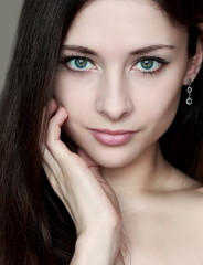 Fashion portrait of woman with sexy look holding face and long h