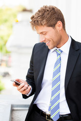 Geschäftsmann liest erfreut SMS