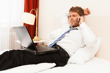 Geschäftsmann mit Computer und Telefon im Hotel