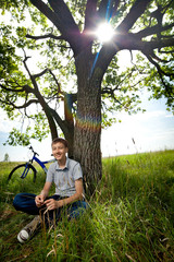 A teenager with a bicycle in the park on the grass