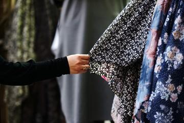 Woman choosing clothes at market
