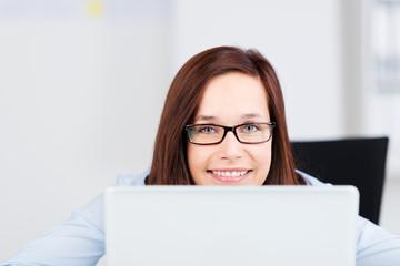 lächelnde frau mit brille schaut über laptop