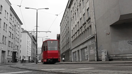 Foto op Canvas Rood, zwart, wit Red tram in the bw city.