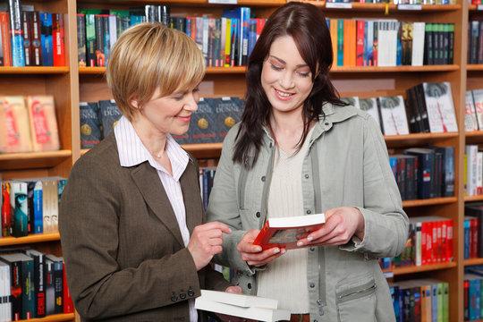 Verkäuferin berät Kundin in einer Buchhandlung
