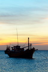 the fishing boat in the sea at a sunset