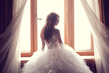 The beautiful bride against a window indoors