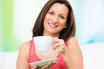 frau trinkt mit freude einen milchkaffee