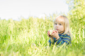 Adorable baby eat red apple sitting on grass in park