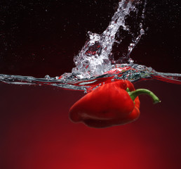 Red pepper falling into water. Background in the same tone