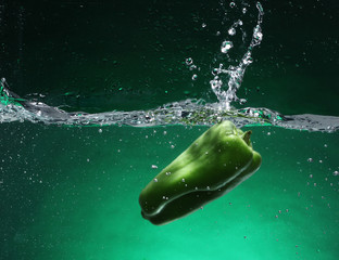 Green pepper falling into water. Green background