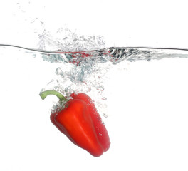 Red pepper falling into water over white background