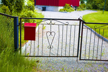 Red mailbox at a gate
