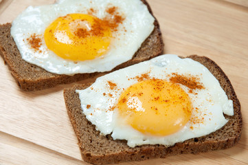 Close-up of two toasts with fried eggs, studio shot