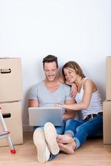 paar mit laptop sitzt zwischen kartons