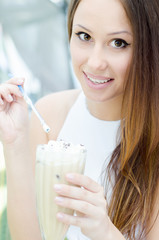 Young woman drinking cocktail in a cafe outdoors